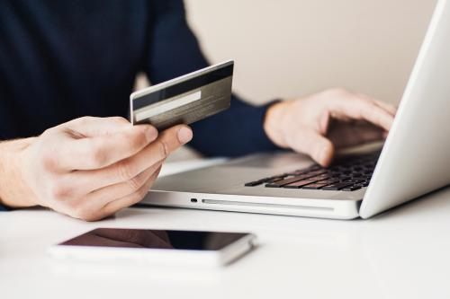 Male hand holding credit card in front of laptop.