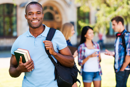 African American College Student holding books and a backpack with campus and other students in the background.