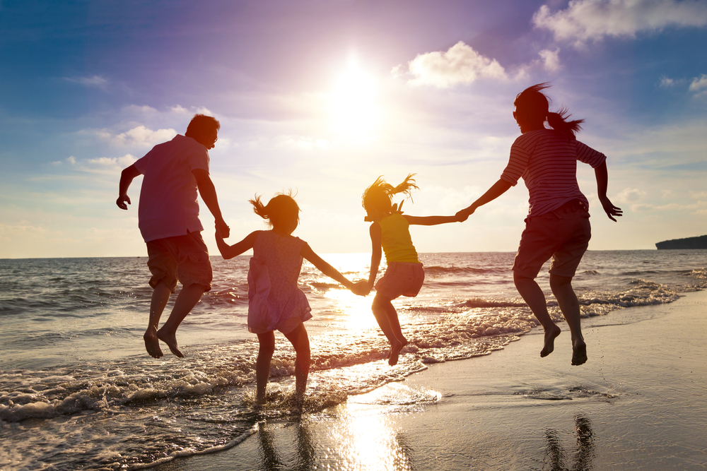 Family of four on the beach jumping in the water with sun shining in the background.