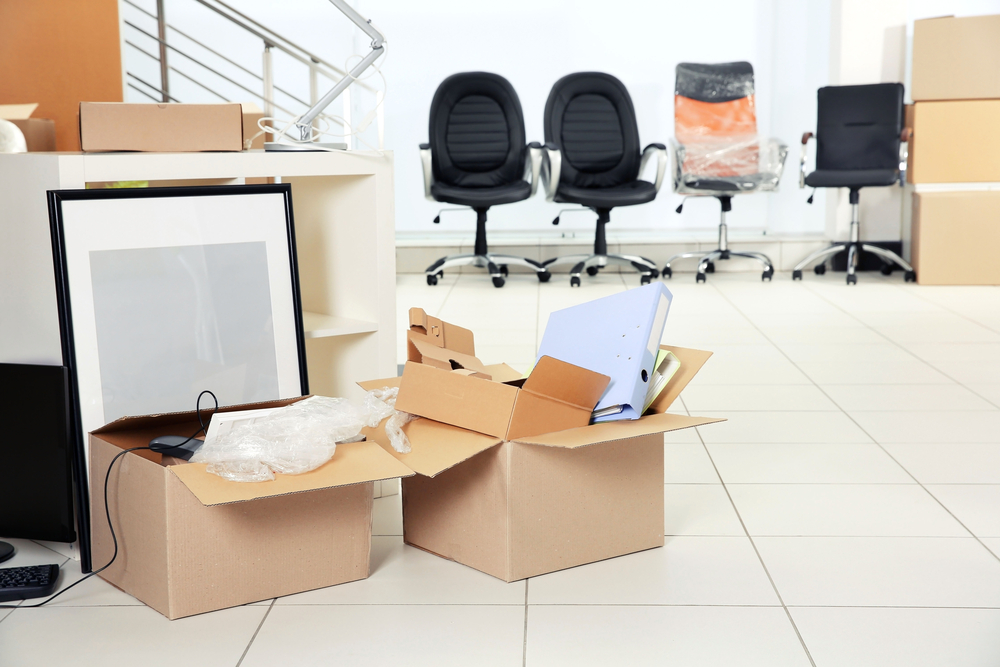 Image Depicting Move_in to New Office with chairs, boxes with papers, framed picture.
