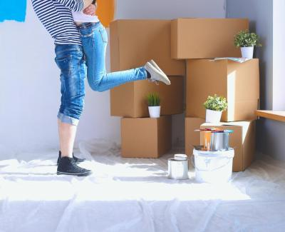 Image showing legs of a man holding a woman with moving boxes and plants in the background.